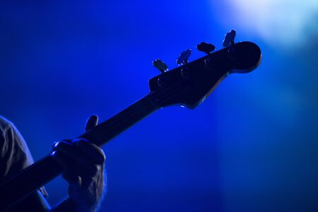 Silhouette of a musician playing on a bass guitar in blue stage lights Stock Photo