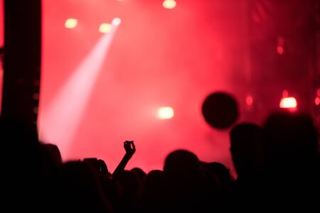 Silhouette of concert crowd against stage lights Stock Photo