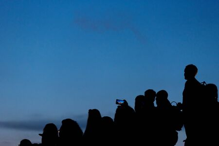 Silhouette of crowd of people against blue sky Stock Photo