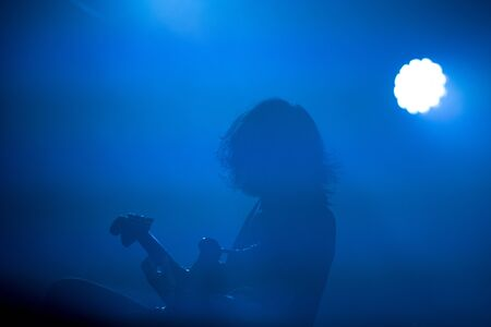 Silhouette of a guitarist in blue stage lights Stock Photo