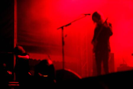 Blurred guitarist playing in red stage lights Stock Photo