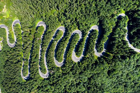 Aerial top view of a winding road in green forest by drone Imagens