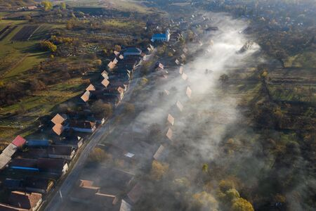 High angle view of a village in Transylvania. Aerial drone view of early morning haze, smoke, fog and sunrise lights. Manastireni, Romania