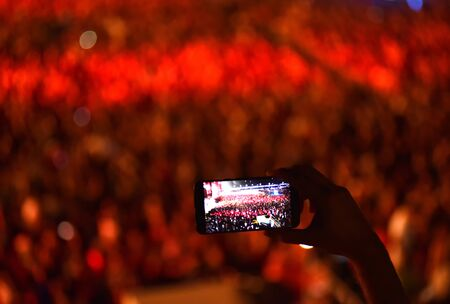 Hand holding smart phone and recording concert at music festival 版權商用圖片