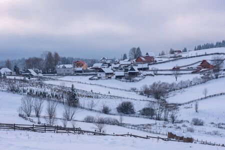 Alpine village in Transylvania, Romania. Snow covered houses in wintertime
