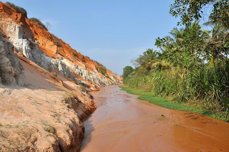 Fairy Stream (Suoi Tien), Mui Ne, Vietnam. The small stream is the place where the desert meets the jungle. Geological attraction with red and white sandstone Фото со стока