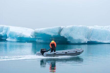 JOKULSARLON, ICELAND - MAY 23, 2019: Ranger guard patrolling in a boat at Jokulsarlon glacial lagoon