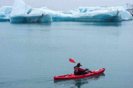 JOKULSARLON, ICELAND - MAY 22, 2019: Man paddling in a kayak in the freezing waters of Jokulsarlon glacier lagoon between icebergs
