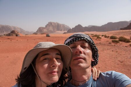 Couple making a selfie photo in Wadi Rum desert, Jordan. Woman wearing hat and the man a keffiyeh Palestinain scarf
