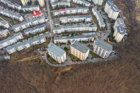 Aerial view of urban environment, city taking place of nature. Expanding flat of blocks occupy virgin forest. Cluj Napoca, Romania