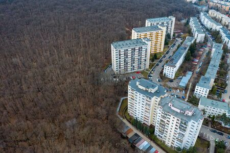 Aerial view of urban environment, city expansion against nature. Expanding flat of blocks from the communist period occupy virgin forest. Cluj Napoca, Romania