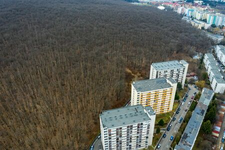Drone view of urban environment, city taking place of nature. Expanding flat of blocks occupy virgin forest. Cluj Napoca, Romania