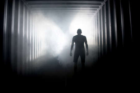 Silhouette of a man in a dark hazy underground corridor. Light at the end of the tunnel