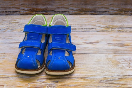 children s feet: Correct childrens orthopedic shoes. On wooden background