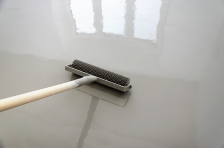 Self-leveling epoxy. Leveling with a mixture of cement floors with a roller. Stock Photo