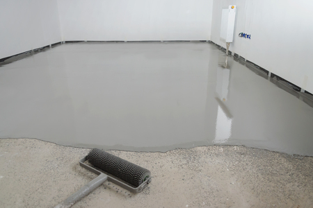 Self-leveling epoxy. Leveling with a mixture of cement floors. 免版税图像