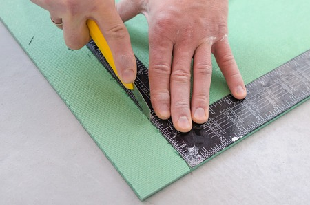 Man cuts the sound insulation Board with a knife. Eco plates from the noise.