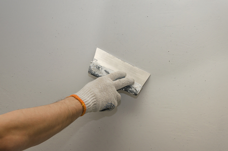 Work putty walls. The alignment of the walls with a trowel
