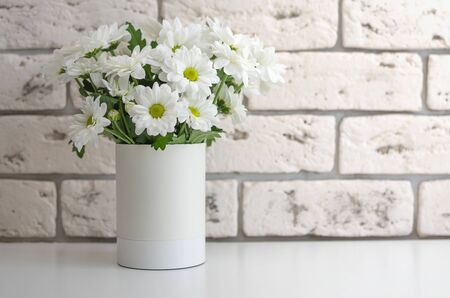 White chrysanthemums in a vase on a stone background. Flowers on the table close-up. Stockfoto