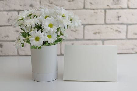 Flowers on the table with a greeting card close-up.White chrysanthemums in a vase on a stone background.
