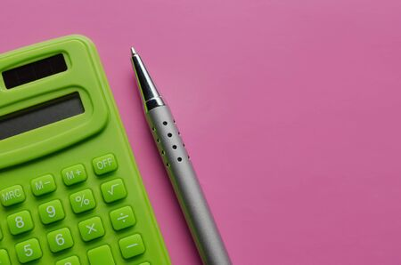 The calculation of the budget, taxes and the cost of the calculator on a pink background. Top view of calculator with pen .