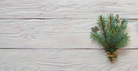 Fir tree branches and pine cones on wooden white background.