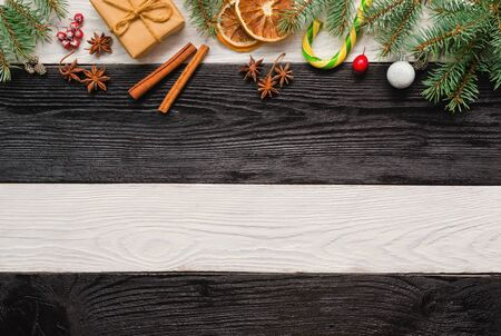 Festive Christmas greeting card with fir branches and pine cones on wooden dark, black and white background. Flat lay, top view, copy space.