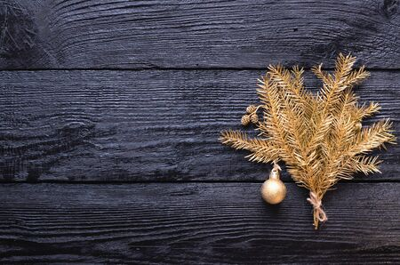 Festive Christmas greeting card with the Golden spruce fir branches and pine cones on wooden dark, black background. Flat lay, top view, copy space.