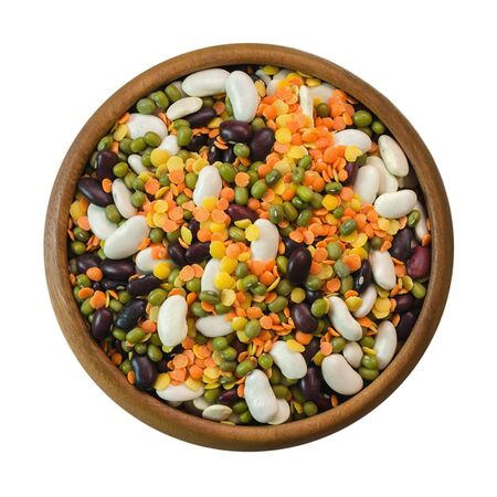Various dried legumes in a wooden cup: bean, lentils, pea, chickpea, mung bean, isolated on white background. Top view