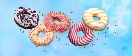 Flying doughnuts. Sweet and colourful donuts on blue background .