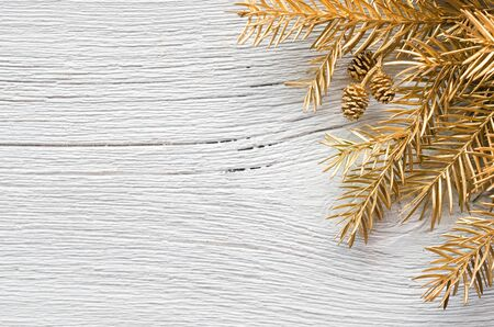 Festive Christmas greeting card with golden fir branches and pine cones on wooden white background. Flat lay, top view, copy space.