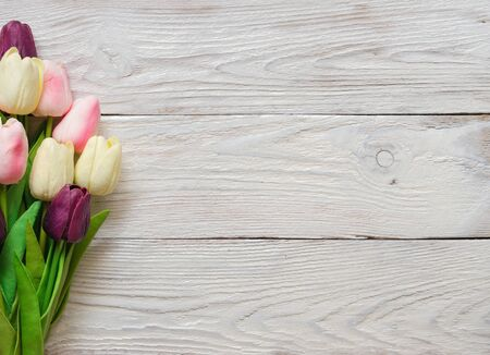 Beautiful Tulip flowers on a white wooden textured background. Spring bouquet. Flat lay, top view, copy space.