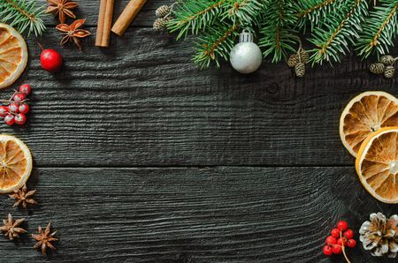 Christmas fir tree branches and pine cones on wooden dark, black background. Фото со стока