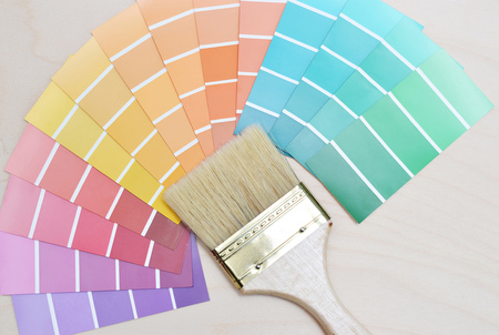 refurbishing: color palette and brush on a wooden background.