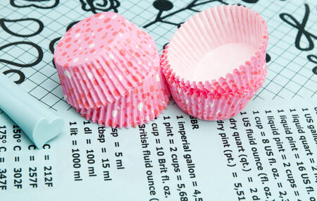 Colorful polka dot cupcake wrappers with color coordinated baking supplies . Closeup with shallow dof. photo