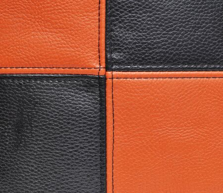 orange texture: Black and orange leather texture decorated with seams Stock Photo
