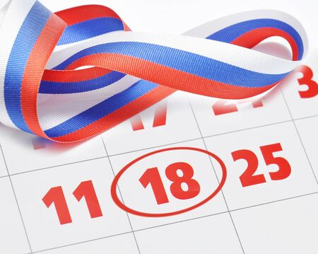 Ribbon bow in colors of Russian flag on the calendar with the election date. Stock Photo