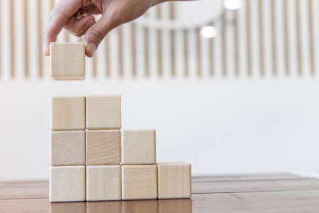 Arrange the wooden blocks into steps, higher the marketing strategy the more effort is required, Ladder of success, Driving business at the peak concept. Archivio Fotografico