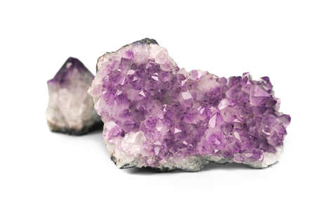 Two raw natural purple amethysts cluster crystals isolated on white background. Big sparkle druse and small gemstone. Stockfoto