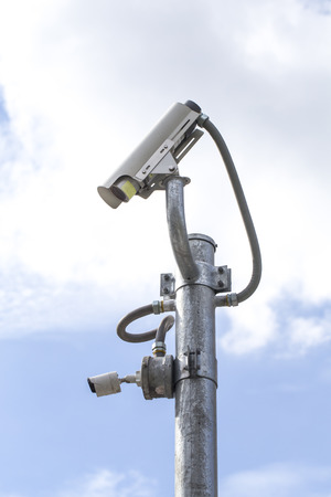 city surveillance: Outdoor CCTV Camera on the Pole with Blue Sky Stock Photo