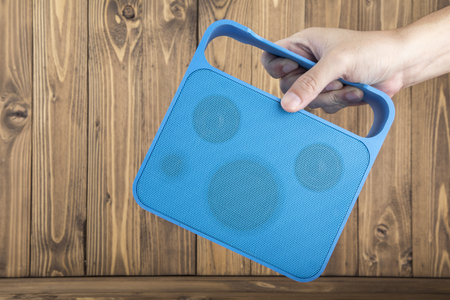 speaker: Mans Hand Carrying Blue Handy Speaker on Wooden Background