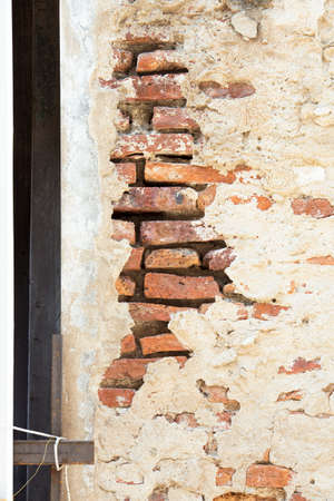 cracked cement: Cracked Cement Wall with Orange Bricks Inside Stock Photo