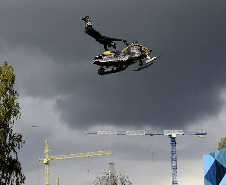 Motorcycle stuntman flies past the cathedral.