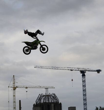 Motorcycle stuntman flies past the cathedral. 写真素材 - 132061598