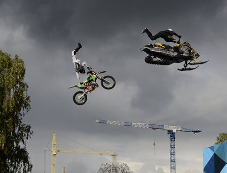 Stunt motorcyclists perform against the backdrop of the Orthodox Cathedral under construction in Chelyabinsk, Russia. 写真素材