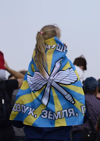 A girl on her fathers shoulders at an air festival in Chelyabinsk.