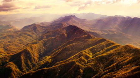 high view: Aerial view of beautiful mountain range with warm sunlight.