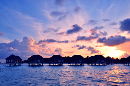 morning blue hour: Sunrise over water bungalows on a cloudy day at the end of rainy season in Maldives.