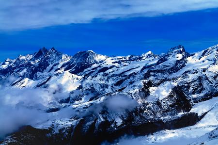 swiss alps: Aerial view of beautiful Swiss Alps surrounded by floating cloud in Zermatt, Switzerland.