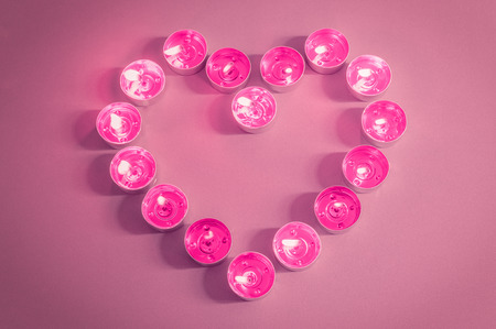 Flaming pink tealight candles forming a heart shape on vintage pink background. Stock Photo